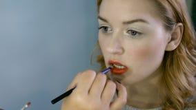 Επαγγελματικός καλλιτέχνης makeup που συνεργάζεται με την όμορφη νέα γυναίκα φιλμ μικρού μήκους