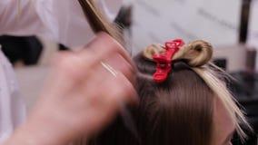 Επαγγελματικός κομμωτής που κάνει ένα hairdo σε ένα ξανθομάλλες πρότυπο απόθεμα βίντεο