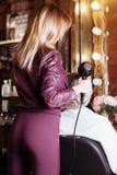 Επαγγελματικός κομμωτής που χρησιμοποιεί hairdryer ενώ τρίχα που ορίζει το θηλυκό πελάτη της Όμορφη νέα γυναίκα που παίρνει ένα ν στοκ φωτογραφίες με δικαίωμα ελεύθερης χρήσης