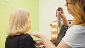 Επαγγελματικός κομμωτής, στιλίστας που κάνει hairstyle για τον ανώτερο ψεκασμό γυναικών με τη λάκκα για τον καθορισμό Ομορφιά και απόθεμα βίντεο