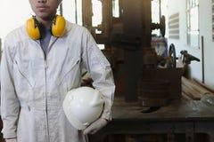 Επαγγελματικός νέος ασιατικός εργαζόμενος με την ομοιόμορφη στάση ασφάλειας στο εργοστάσιο με το κάθετο υπόβαθρο μηχανών πριονιών στοκ φωτογραφίες με δικαίωμα ελεύθερης χρήσης