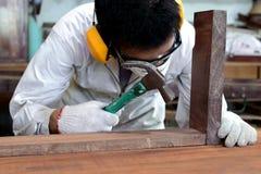 Επαγγελματικός ξυλουργός με το ομοιόμορφο σφυρί εκμετάλλευσης ασφάλειας στον ξύλινο πάγκο εργασίας στο εργαστήριο ξυλουργικής Στοκ Φωτογραφία