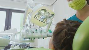 Επαγγελματικός οδοντίατρος που θεραπεύει τα δόντια παιδιών, επεξεργασία αποσύνθεσης δοντιών, σύγχρονη κλινική φιλμ μικρού μήκους