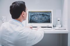 Επαγγελματικός οδοντίατρος που κοιτάζει επίμονα στην οθόνη του υπολογιστή στοκ φωτογραφία με δικαίωμα ελεύθερης χρήσης