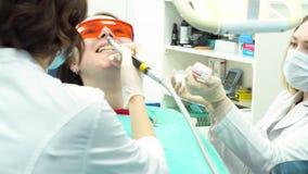 Επαγγελματικός οδοντικός καθαρισμός των θηλυκών υπομονετικών δοντιών στην οδοντική κλινική, έννοια ιατρικής MEDIA Να κάνει οδοντι απόθεμα βίντεο