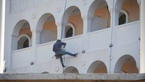 Επαγγελματικός ορειβάτης στην εργασία Επισκευή της πρόσοψης του κτηρίου Ορειβάτης ζωγράφων που εργάζεται στην πρόσοψη σπιτιών Γυψ απόθεμα βίντεο