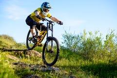 Επαγγελματικός ποδηλάτης στο κίτρινο οδηγώντας ποδήλατο μπλουζών και κρανών κάτω από το δύσκολο Hill Ακραία αθλητική έννοια στοκ φωτογραφία με δικαίωμα ελεύθερης χρήσης