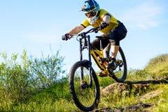 Επαγγελματικός ποδηλάτης στο κίτρινο οδηγώντας ποδήλατο μπλουζών και κρανών κάτω από το δύσκολο Hill Ακραία αθλητική έννοια στοκ εικόνες με δικαίωμα ελεύθερης χρήσης