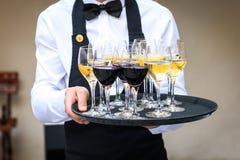 Επαγγελματικός σερβιτόρος στο μαύρο ομοιόμορφο εξυπηρετώντας κόκκινο και άσπρο κρασί Στοκ εικόνες με δικαίωμα ελεύθερης χρήσης
