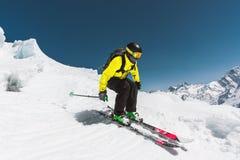 Επαγγελματικός σκιέρ με την ταχύτητα πρίν πηδά από τον παγετώνα το χειμώνα ενάντια στο μπλε ουρανό και τα βουνά στοκ εικόνα