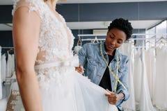 Επαγγελματικός σχεδιαστής γαμήλιων φορεμάτων που εγκαθιστά τη νυφική εσθήτα στη γυναίκα Στοκ φωτογραφία με δικαίωμα ελεύθερης χρήσης