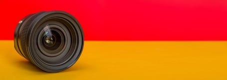 Επαγγελματικός φακός καμερών στο κόκκινο και κίτρινο πρότυπο υποβάθρου στοκ φωτογραφία με δικαίωμα ελεύθερης χρήσης