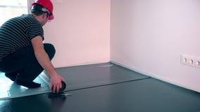 Επαγγελματικό άτομο εργαζομένων που βάζει το υπόστρωμα για τη φυλλόμορφη εγκατάσταση δαπέδων απόθεμα βίντεο