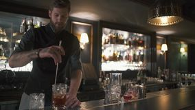 Επαγγελματικό γενειοφόρο bartender που αναμιγνύει το ρούμι και τον πάγο στο γυαλί με το μακρύ ραβδί μετάλλων Μπάρμαν που κατασκευ φιλμ μικρού μήκους