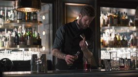 Επαγγελματικό γενειοφόρο bartender χύνοντας ρούμι στην κούπα μετάλλων, έπειτα στο γυαλί Μπάρμαν που κατασκευάζει το κοκτέιλ στο σ απόθεμα βίντεο