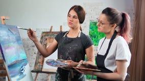 Επαγγελματικό ειδικευμένο θηλυκό χρωματίζοντας νέο κορίτσι διδασκαλίας καλλιτεχνών δασκάλων στο μέσο πυροβολισμό στούντιο απόθεμα βίντεο