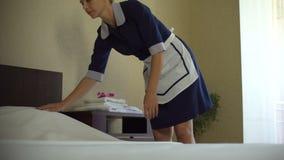 Επαγγελματικό κορίτσι που κάνει το κρεβάτι στο δωμάτιο ξενοδοχείου, που αλλάζει τα κλινοσκεπάσματα, οικοκυρική φιλμ μικρού μήκους