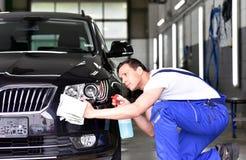 Επαγγελματικό πλύσιμο αυτοκινήτων - ο εργαζόμενος σε μια εμπορία αυτοκινήτων γυαλίζει Στοκ εικόνες με δικαίωμα ελεύθερης χρήσης