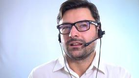 Τα χαμογελώντας άτομα που εργάζονται στη εξυπηρέτηση πελατών υποστηρίζουν στο γραφείο Επαγγελματικό σε απευθείας σύνδεση και τηλε απόθεμα βίντεο