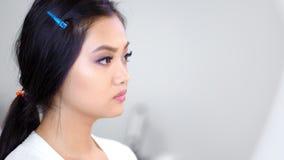 Επαγγελματικό visagist πλάγιας όψης που ισχύει brow makeup χρησιμοποιώντας τη βούρτσα στο στούντιο ομορφιάς φιλμ μικρού μήκους