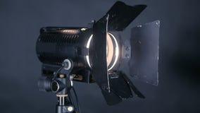 Επαγγελματικά spotlighs, φω'τα στούντιο για τη κινηματογραφία, παραγωγή TV σε ένα μαύρο υπόβαθρο, που ανάβει και μακριά απόθεμα βίντεο
