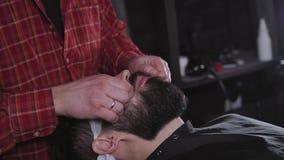 Επαγγελματική γενειάδα καλλωπισμού κινηματογραφήσεων σε πρώτο πλάνο με το ψαλίδι σε ένα Barbershop Έννοια Hipster Πορτρέτο ενός γ φιλμ μικρού μήκους