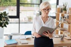 Επαγγελματική σκληρή εργαζόμενη επιχειρηματίας που διαβάζει μια έκθεση στοκ εικόνες