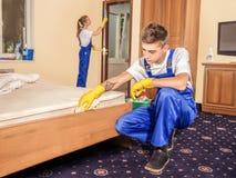 Επαγγελματικοί καθαριστές που καθαρίζουν τα έπιπλα και το πάτωμα στο δωμάτιο Στοκ φωτογραφία με δικαίωμα ελεύθερης χρήσης