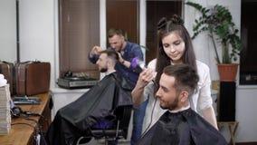 Επαγγελματικοί κομμωτές που κάνουν το μοντέρνο hairdo στα άτομα που κάθονται στο σαλόνι φιλμ μικρού μήκους