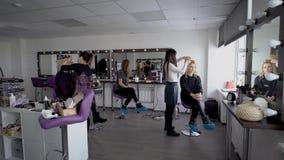 Επαγγελματικοί στιλίστας και makeup καλλιτέχνης τρίχας στο μεγάλο στούντιό τους που προετοιμάζουν τα πρότυπα πρίν πηγαίνει στην ε απόθεμα βίντεο