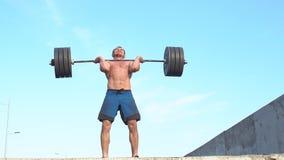 Επαγγελματικός αθλητικός τύπος που προετοιμάζεται για την κατάρτιση με ένα barbell απόθεμα βίντεο