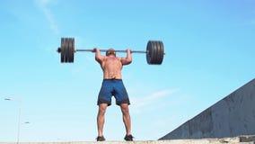 Επαγγελματικός αθλητικός τύπος που προετοιμάζεται για την κατάρτιση με ένα barbell κίνηση αργή φιλμ μικρού μήκους