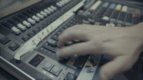 Επαγγελματικός ακουστικός χειριστής που εργάζεται στα ακουστικά εξογκώματα αναμικτών απόθεμα βίντεο