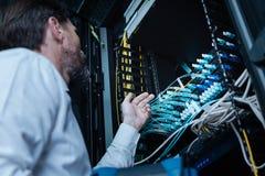 Επαγγελματικός αρσενικός τεχνικός που εξετάζει τα καλώδια Ethernet Στοκ Φωτογραφίες
