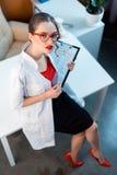 Επαγγελματικός γιατρός στα γυαλιά που κρατά το σημειωματάριο Στοκ Εικόνα