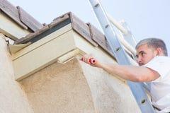 Επαγγελματικός ζωγράφος που χρησιμοποιεί το μικρό κύλινδρο στη λωρίδα σπιτιών χρωμάτων στοκ εικόνες με δικαίωμα ελεύθερης χρήσης