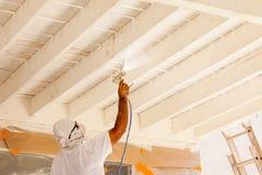 Επαγγελματικός ζωγράφος σπιτιών που φορά το του προσώπου χρώμα ψεκασμού προστασίας στοκ εικόνες