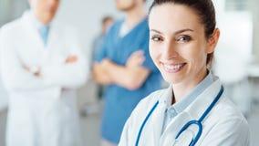 Επαγγελματικός θηλυκός γιατρός που θέτει και που χαμογελά Στοκ φωτογραφία με δικαίωμα ελεύθερης χρήσης