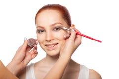 Επαγγελματικός καλλιτέχνης σύνθεσης που κάνει τη γοητεία με το κόκκινο πρότυπο τρίχας makeup Απομονωμένο υπόβαθρο Στοκ Φωτογραφία