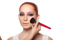 Επαγγελματικός καλλιτέχνης σύνθεσης που κάνει τη γοητεία με το κόκκινο πρότυπο τρίχας makeup Απομονωμένο υπόβαθρο Στοκ φωτογραφίες με δικαίωμα ελεύθερης χρήσης