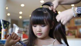 Επαγγελματικός καλλιτέχνης makeup που συνεργάζεται με το χαριτωμένο ασιατικό παιδί απόθεμα βίντεο
