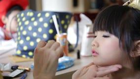 Επαγγελματικός καλλιτέχνης makeup που συνεργάζεται με το χαριτωμένο ασιατικό παιδί φιλμ μικρού μήκους