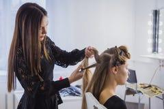 Επαγγελματικός κομμωτής που κάνει hairstyle για τη νέα όμορφη γυναίκα με μακρυμάλλη Στοκ φωτογραφία με δικαίωμα ελεύθερης χρήσης