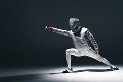 Επαγγελματικός ξιφομάχος στην περίφραξη της μάσκας με rapier που στέκεται σε θέση Στοκ εικόνες με δικαίωμα ελεύθερης χρήσης