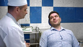 Επαγγελματικός οδοντίατρος που μιλά με το νέο αρσενικό ασθενή του στην οδοντική κλινική απόθεμα βίντεο