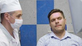 Επαγγελματικός οδοντίατρος που μιλά στον ασθενή του φιλμ μικρού μήκους