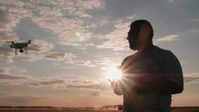 Επαγγελματικός πειραματικός του κηφήνα οδηγεί το copter στο ηλιοβασίλεμα, σκιαγραφία απόθεμα βίντεο