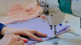 Επαγγελματικός ράφτης, ράβοντας ενδύματα σχεδιαστών μόδας με τη ράβοντας μηχανή στοκ εικόνες