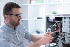 Επαγγελματικό άτομο που επισκευάζει και που συγκεντρώνει έναν υπολογιστή Στοκ Εικόνες