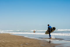Επαγγελματικό αρσενικό surfer που φέρνει την ιστιοσανίδα του περπατώντας κατά μήκος μιας παραλίας άμμου Στοκ Εικόνα